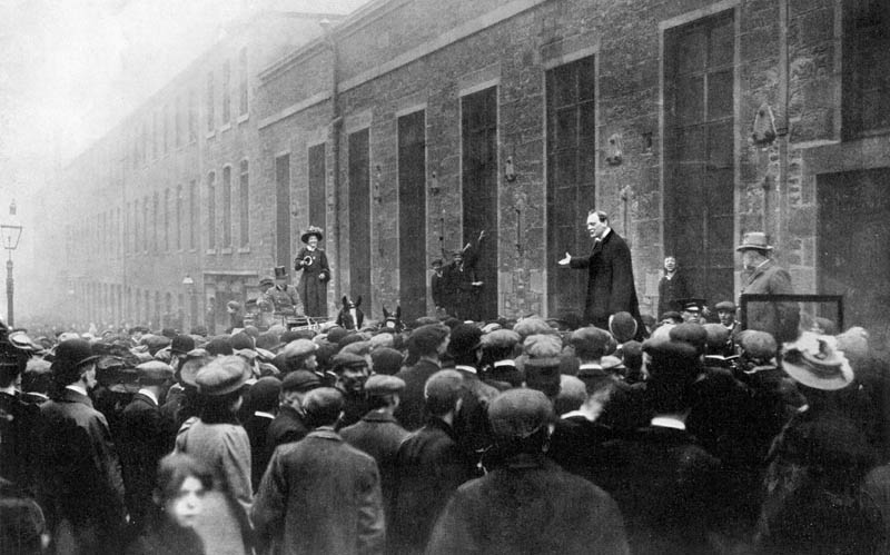 "A photograph of Winston Churchill addressing a lunchtime meeting of workmen at a large factory in Dundee, Scotland, as Liberal candidate in the Dundee by-election.  Miss Dorothy Molony, an Irish suffragist and member of the Women's Freedom League, arrived in a carriage and drowned the speaker's voice by repeatedly ringing a a handbell, stating that he should not be allowed to speak until he had apologised for some recent remarks he had made about women politicians.  Churchill struggled to be heard, but eventually had to abandon his speech, saying: ""If she thinks that is a reasonable argument she may use it. I don't care. I bid you good afternoon.""  WSPU members Emmeline Pankhurst, Christabel Pankhurst and Mary Gawthorpe were also active during the campaign, holding meetings in the town.  Churchill won the seat with a comfortable majority, and represented Dundee until 1922.      Date: May 1908"